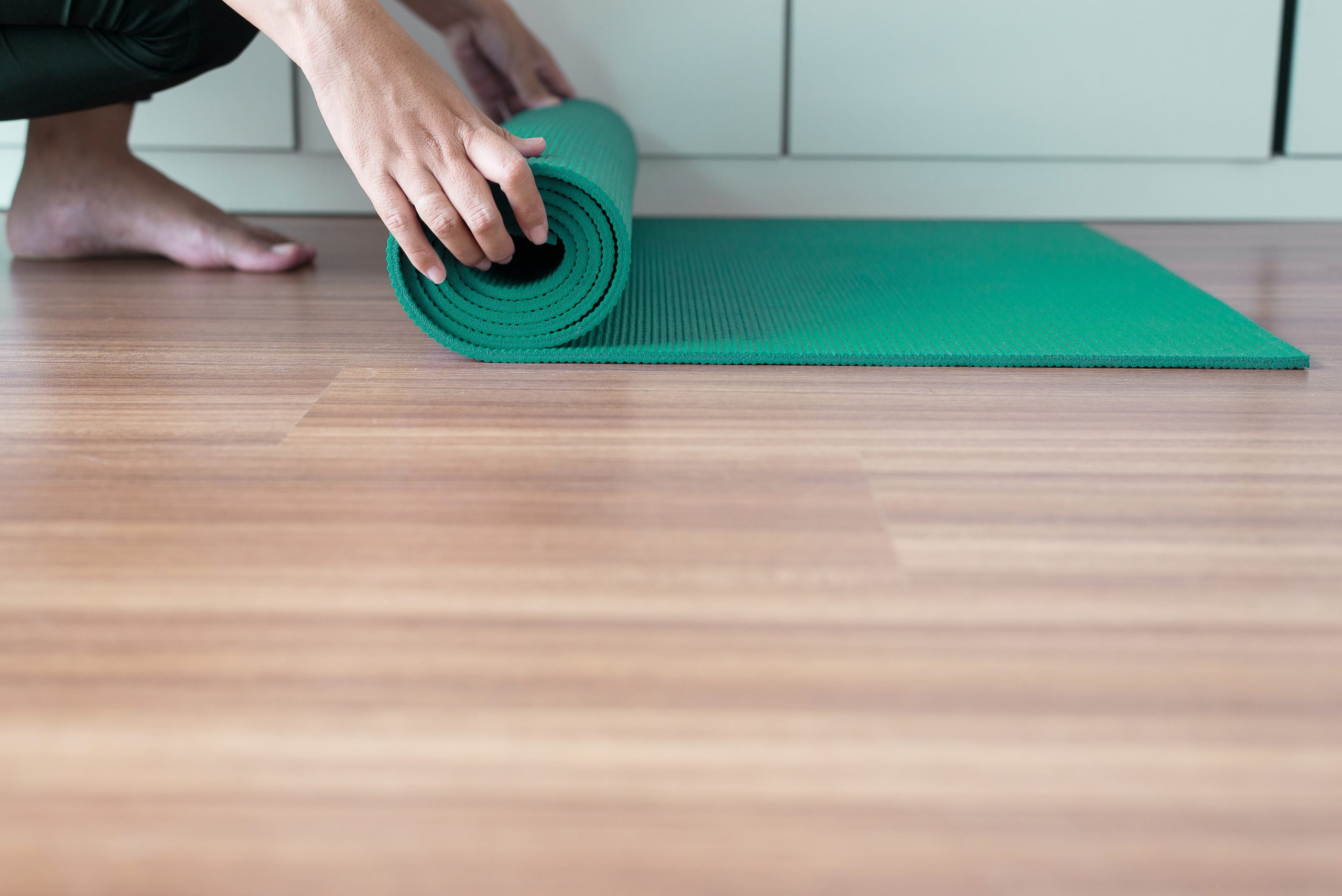 Woman hand rolling or folding green yoga mat after a workout